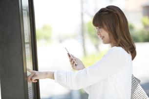 バス停で時刻表を確認する女性の写真素材 [FYI04641973]