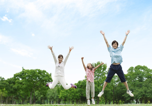 ジャンプする家族3人の写真素材 [FYI04642143]