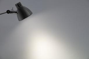 デスクスタンドが照らす白い壁の写真素材 [FYI04642548]