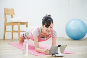 タブレットを見てトレーニングをする女性の写真素材 [FYI04642666]
