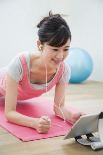 タブレットを見てトレーニングをする女性の写真素材 [FYI04642667]