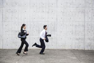 走るビジネスウーマンとビジネスマンの写真素材 [FYI04642792]