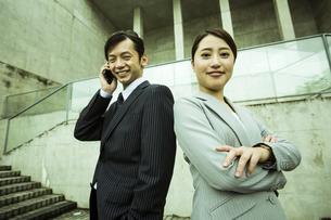 スマートフォンで電話をするビジネスマンと腕組みをするビジネスウーマンの写真素材 [FYI04642838]