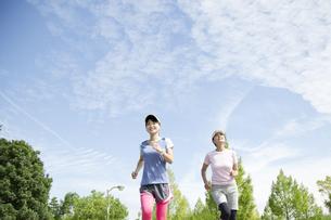 青空の下でジョギングする親子の写真素材 [FYI04642840]
