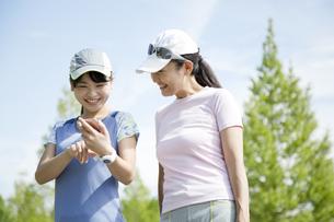 運動中にスマートフォンを見る親子の写真素材 [FYI04642856]