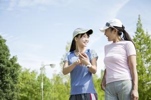 運動中にスマートフォンを片手に会話をする親子の写真素材 [FYI04642857]