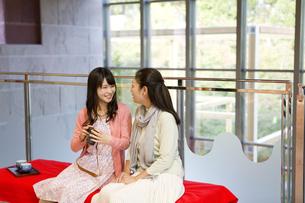 カメラを片手に会話をする娘と母親の写真素材 [FYI04642970]