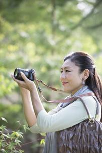 デジタルカメラを構える中年女性の写真素材 [FYI04642991]