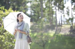 日傘をさす中年女性の写真素材 [FYI04643001]
