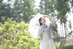 日傘をさす笑顔の中年女性の写真素材 [FYI04643003]