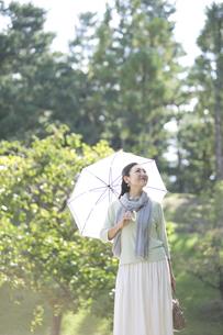 日傘をさす笑顔の中年女性の写真素材 [FYI04643004]