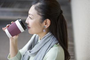 ホットドリンクを飲む中年女性の写真素材 [FYI04643021]