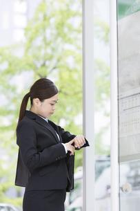 時計を見ているスーツを着た日本人女性の写真素材 [FYI04643052]