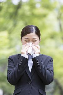鼻をかむスーツを着た日本人女性の写真素材 [FYI04643078]