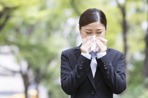 鼻をかむスーツを着た日本人女性の写真素材 [FYI04643080]