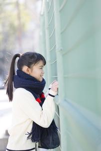 フェンスから眺める女子校生の写真素材 [FYI04643253]