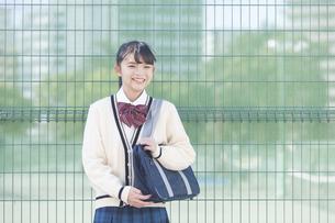 フェンスの前を立つ女子校生の写真素材 [FYI04643257]