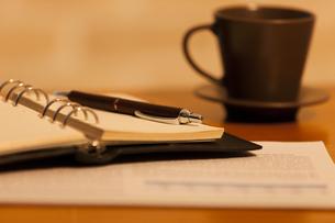 テーブルに置かれたコーヒーと手帳の写真素材 [FYI04643905]
