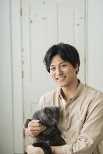 リモートワークをする男性と猫の写真素材 [FYI04644130]