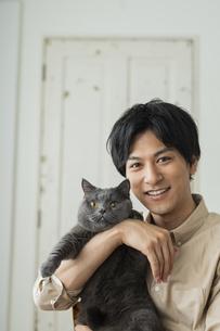 リモートワークをする男性と猫の写真素材 [FYI04644131]