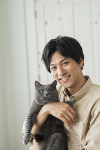 リモートワークをする男性と猫の写真素材 [FYI04644132]