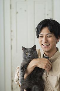 リモートワークをする男性と猫の写真素材 [FYI04644133]
