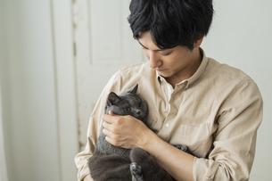 リモートワークをする男性と猫の写真素材 [FYI04644144]