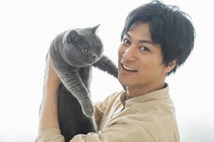 リモートワークをする男性と猫の写真素材 [FYI04644213]