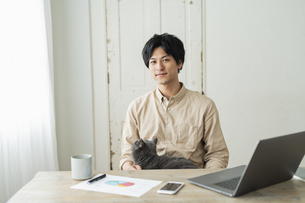 リモートワークをする男性と猫の写真素材 [FYI04644227]
