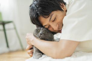 リモートワークをする男性と猫の写真素材 [FYI04644797]