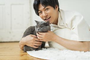 リモートワークをする男性と猫の写真素材 [FYI04644800]