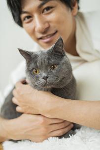 リモートワークをする男性と猫の写真素材 [FYI04644803]