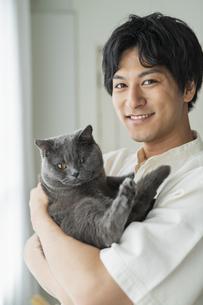 リモートワークをする男性と猫の写真素材 [FYI04644831]