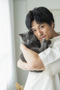 リモートワークをする男性と猫の写真素材 [FYI04644832]