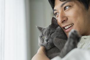 リモートワークをする男性と猫の写真素材 [FYI04644837]