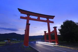 黎明の生島足島神社の大鳥居と自動車のヘッドライトの写真素材 [FYI04645516]