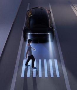 暗闇のなか車が道路横断中の歩行者の前に急停止した。ADAS先進運転システムのコンセプトの写真素材 [FYI04645805]