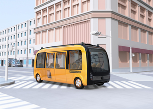 交差点を通過している黄色の自動運転バスのイメージの写真素材 [FYI04645850]