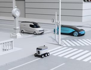 スクランブル交差点を通過する自動運転車と路側帯に走行中の配送ロボットのイメージの写真素材 [FYI04645960]