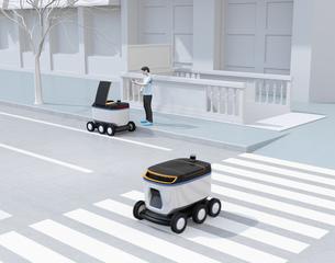 交差点を通過する配送ロボット。その近くにスマホアプリで配送ロボットから荷物を受け取る人がいるの写真素材 [FYI04645969]