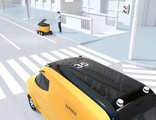 交差点を通過する自動運転宅配車。その近くにスマホアプリで配送ロボットから荷物を受け取る人がいるの写真素材 [FYI04645972]