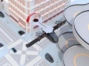 ヘリポートの横から通過する空飛ぶタクシーのイメージ。短距離ライドシェアコンセプトの写真素材 [FYI04645999]
