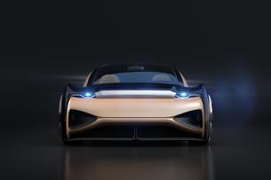 黒バックにメタリックゴールド色の自動運転電気自動車高級サルーンの正面イメージ。オリジナルデザインの写真素材 [FYI04646085]