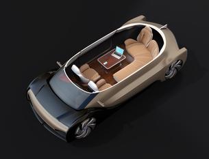 黒バックに自動運転EVのカットモデルイメージ。前列シート後ろ向きに、テーブルにノートPC、スマホの写真素材 [FYI04646099]