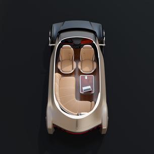 黒バックに自動運転EVのカットモデルイメージ。前列シート後ろ向きに、テーブルにノートPC、スマホの写真素材 [FYI04646101]
