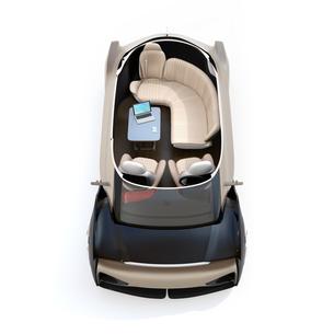 自動運転EVのカットモデルイメージ。前列シート後ろ向きに、テーブルにノートPC、スマホの写真素材 [FYI04646104]