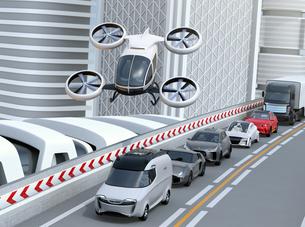 高速道路に渋滞している車列の上空を飛行する自動運転ドローンタクシーのイメージ。空飛ぶ車のコンセプトの写真素材 [FYI04646569]