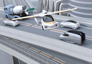 高速道路渋滞中の車列の上に通過するフライングカー(空飛ぶ車)のコンセプトイメージの写真素材 [FYI04646800]