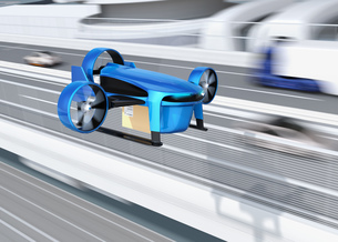 高速道路の横に飛行している青色のVTOL式配達ドローンのイメージ。超高速配達のコンセプトの写真素材 [FYI04646854]