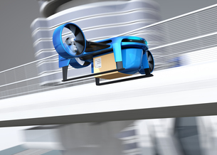 高速道路の横に飛行している青色のVTOL式配達ドローンのイメージ。超高速配達のコンセプトの写真素材 [FYI04646865]